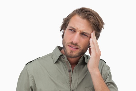 wincing: Man with headache looking away on white background
