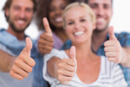 Happy fashionable group giving thumbs up on white background photo