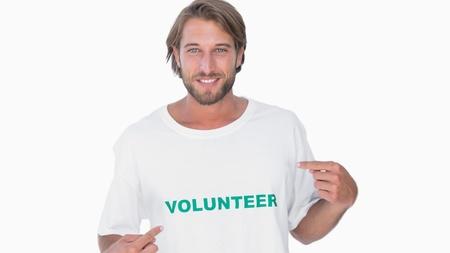 altruism: Hombre que señala a su camiseta de voluntario en el fondo blanco
