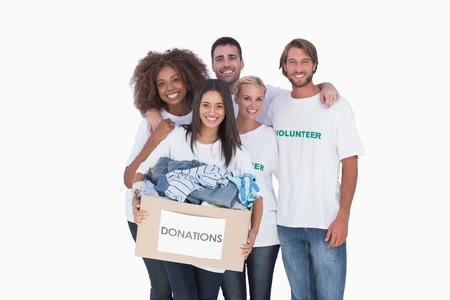 altruismo: Grupo sonriente de voluntarios sosteniendo boxvolunteers donaci�n en el fondo blanco