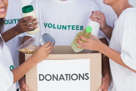 Group of volunteers putting food in donation box photo