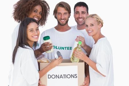 altruismo: Feliz voluntarios que ponen comida en caja para donaciones en el fondo blanco Foto de archivo