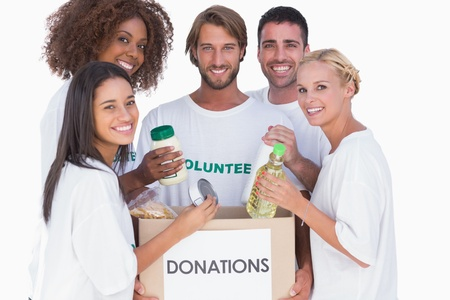 Happy volunteers putting food in donation box on white background photo
