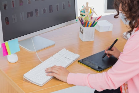 Editor using graphics tablet at her desk in office photo
