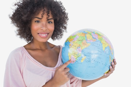 Happy woman pointing to globe on white background photo