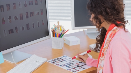 contact sheet: Editor marking the contact sheet at her desk in creative office Stock Photo