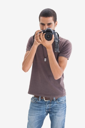 Young man pointing his camera at the camera on white background photo