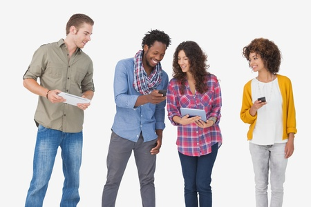 Four stylish friends looking at tablet and holding phones on white background photo