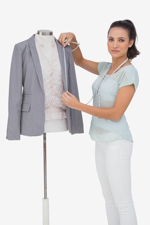 blazer: Fashion designer measuring blazer on white background Stock Photo