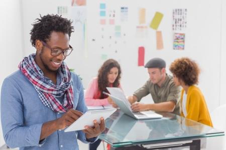 L�chelnde Menschen mit Tablet mit kreativen Team hinter arbeiten in modernen B�ro