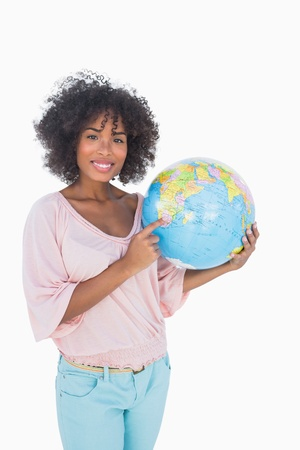 Woman holding and pointing to globe on white background photo