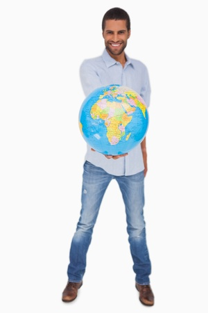 Happy man holding out a globe on white background photo