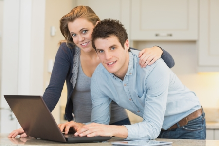 Happy couple on laptop in kitchen photo