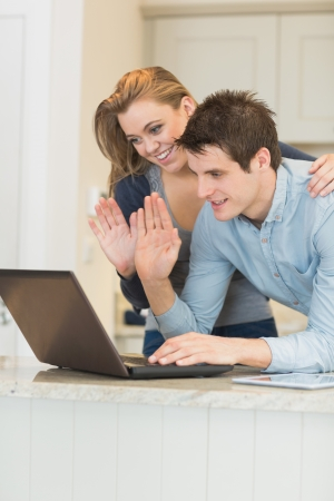 Man and woman use the webcam and wave their hands photo