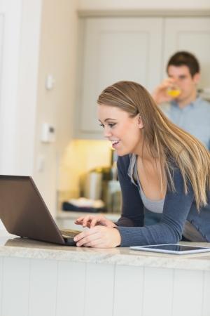 Woman talking via Webcam with man drinking orange juice in kitchen photo