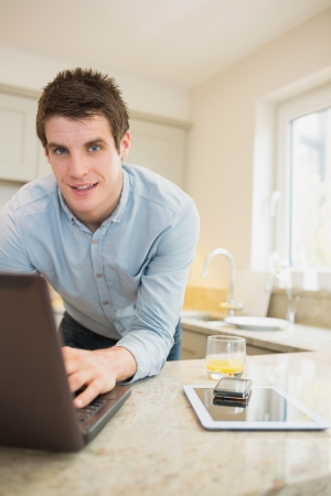 Man typing at the notebook with smartphone and tablet in kitchen photo
