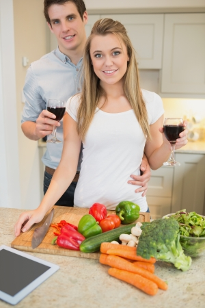 Couple in the kitchen drinking wine with vegetables on chopping board photo