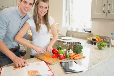 Woman cutting vegetables with man reading the cookery book in kitchen photo