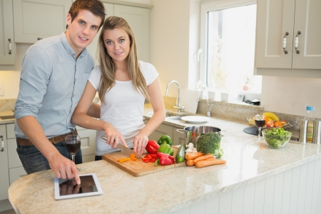 Man pointing on tablet pc wtih woman choppping peppers in kitchen photo