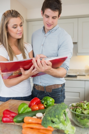 Couple reading cookbook together in kitchen photo