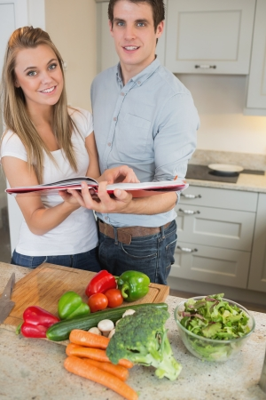 Happy couple with cookery book in kitchen photo