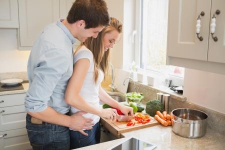 Man praten met de vrouw tijdens het koken in de keuken Stockfoto