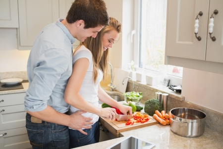 woman cooking: Man talking with woman while cooking in kitchen Stock Photo