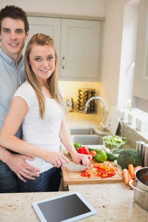 Man and woman cutting vegetables in kitchen photo