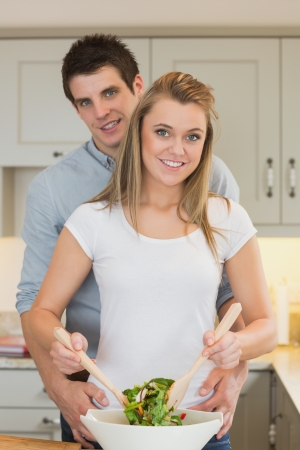 Man and woman preparing a salad in kitchen photo