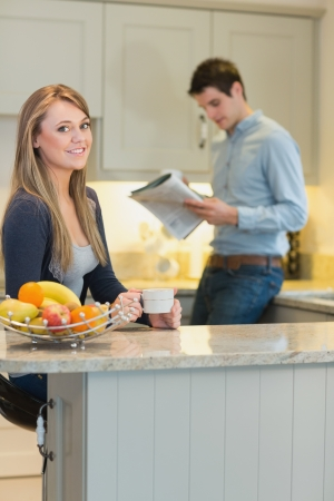 Smiling woman drinking hot drink with man reading newspaper in kitchen photo