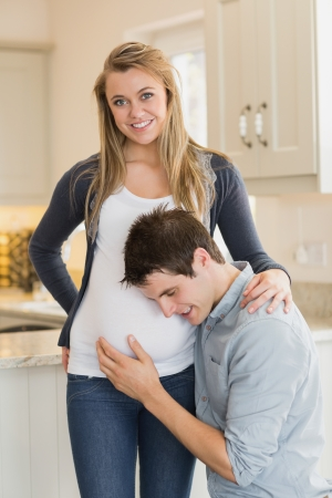 Smiling pregnant woman with husband in kitchen photo