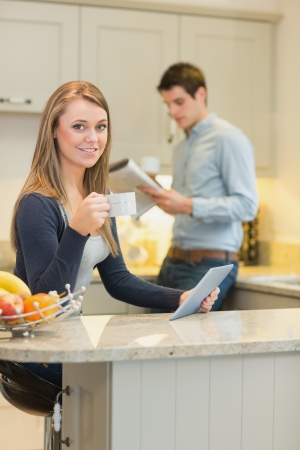 Woman drinking coffee and holding tablet pc in kitchen photo