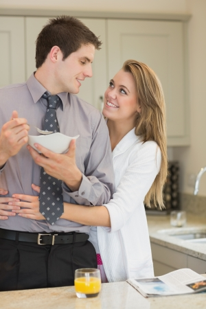 parter: Man eats cereal while parter is embracing him in kitchen