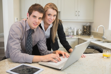 Smiling couple using laptop in kitchen photo