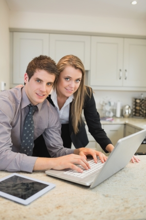 Couple typing on the notebook in kitchen photo