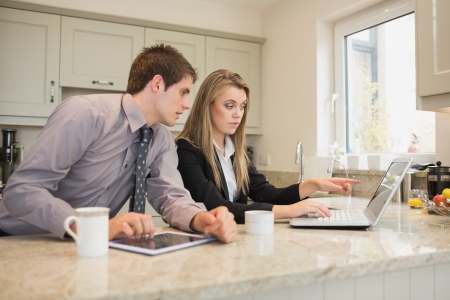 Woman showing her husband something on the laptop in kitchen photo