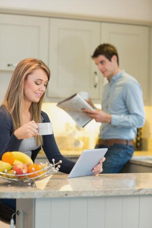 Woman with beverage and tablet computer and man with newspaper in kitchen photo