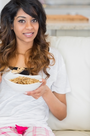Woman eating cereal on sofa photo