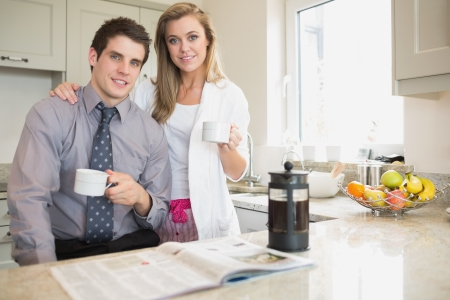 newspaper: Couple reading newspaper and drinking coffee in kitchen Stock Photo