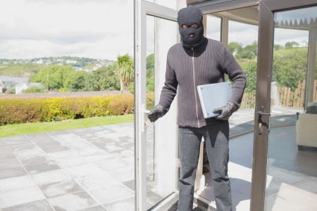 Burglar holding laptop and leaving home Stock Photo - 20517050