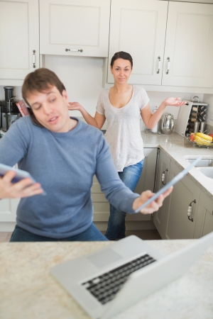 Man busy with technology while his wife wondering why in kitchen photo