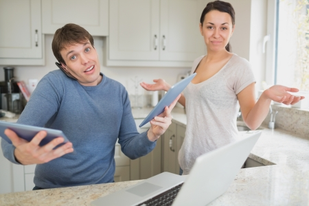 Busy man using two tablets and laptop with wife holding hands up questioning in kitchen  photo