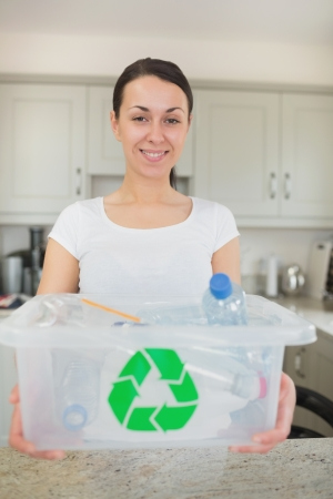 Woman holding full recycling bin in kitchen photo