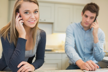 Couple on mobile phones in kitchen photo