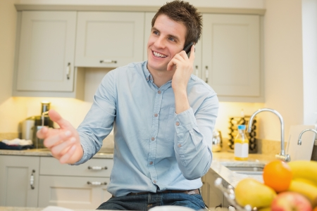 Man gesticulating while calling in kitchen Stock Photo