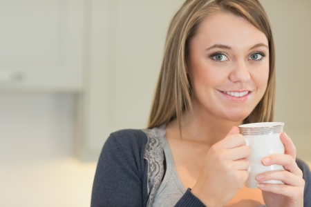 Happy woman drinking coffee in kitchen photo