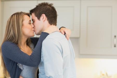 pareja besandose: Los besos y abrazos pareja en la cocina