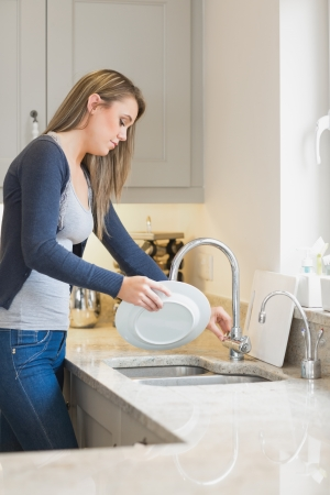 Woman doing the washing up in kitchen photo