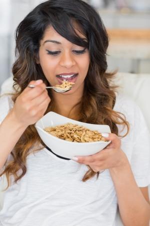 Girl eating cereal on sofa photo