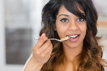 Woman holding a spoon with cereal about to eat photo